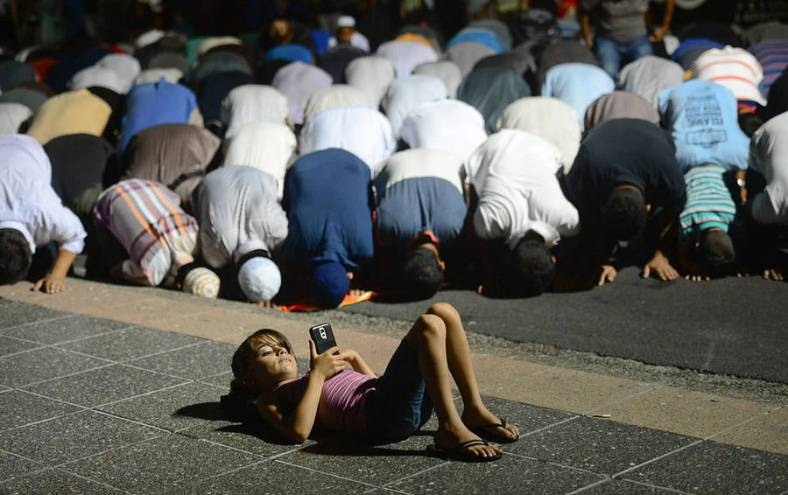 call-to-prayer-a-young-girl-plays-on-her-phone-in-front-of-muslim-men-as-they-take-evening-prayer-in-lakemba-photo-by-jeremy-piperaustralian-life-prize-2015-900x566